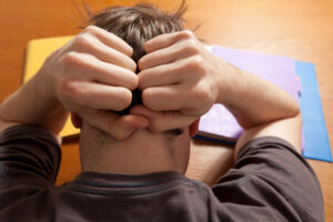 Student or teenager at work at a table, who is stressed or tired or distraught, tearing his hair out